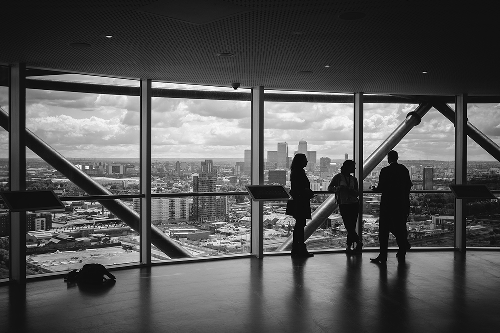 network successfully | group of professionals standing in front  of a large window overlooking the city.