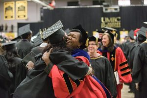 two women hugging at graduation ceremony