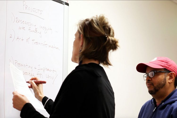 Two students writing transformative ideas on whiteboard.